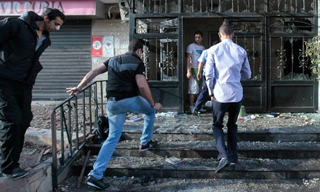Lebanese men step inside a destroyed building that was damaged during clashes in Beirut