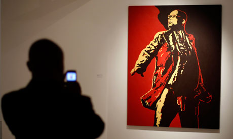 A visitor photographs a painting of South Africa's president Jacob Zuma at an exhibition in Johannesburg, before the picture was vandalised. Photograph: Siphiwe Sibeko/Reuters