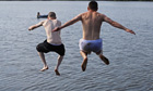 Two boys jump in Pickmere Lake, Knutsford to cool off.