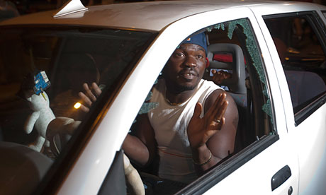 An African migrant in a car with shattered windows after a protest against African refugees