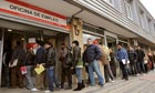 Jobseekers queue outside an employment centre in Madrid