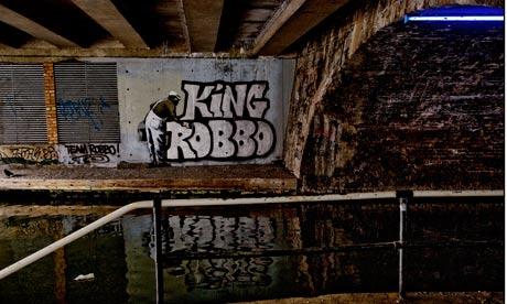 Banksy graffiti and King Robbo graffiti under canal bridge