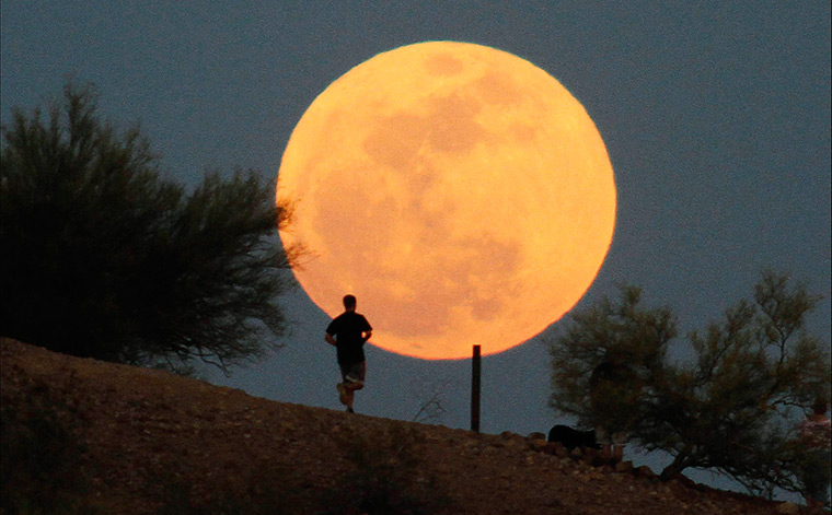 Supermoon: A runner makes his way along a trail at Papago Park in Phoenix, Arizona