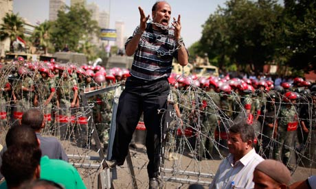 Protester shouts as he stands on top of a barricade in Cairo