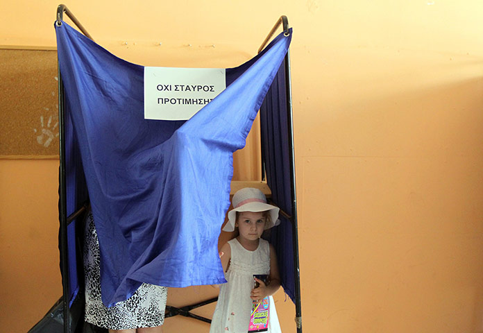 Greek elections: A girl goes to vote with her mother in a polling station in Athens