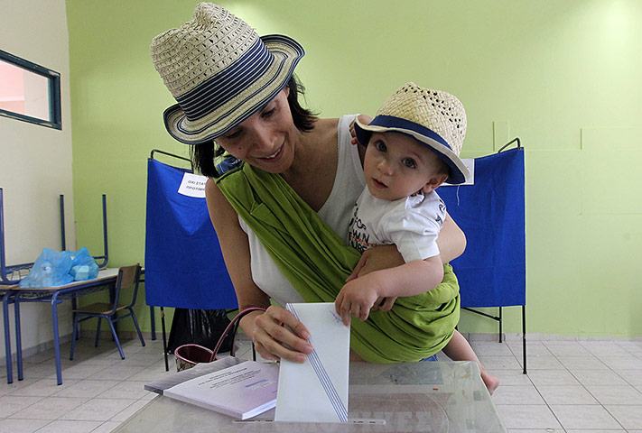 Greek elections: A woman holds her child as she casts her ballot