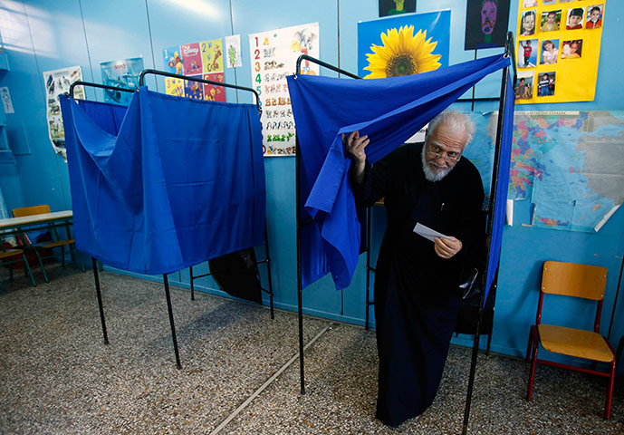 Greek elections: Father Christos holds his ballot paper as he exits the voting booth
