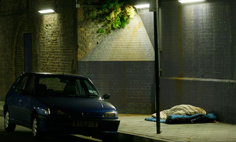 A homeless person sleeps rough under a bridge in central London