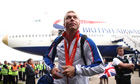 Chris Hoy leaves the plane at Heathrow airport