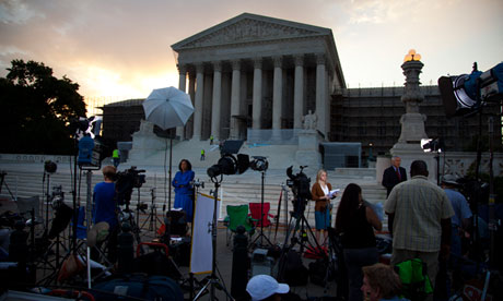 Journalists wait outside the Supreme Court for a landmark decision on health care 