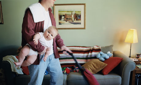 Father holding baby (6-9 months) and vacuuming