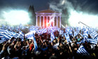 Supporters of the Greek party New Democracy wave flags during a pre-election speech on 3 May