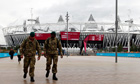 Two soldiers walk through the Olympic park with the Olympic stadium behind them