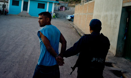 A man is detained by Honduran police officers