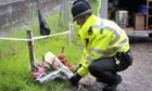 A policeman lays flowers at Pontesbury Hill, near Shrewsbury