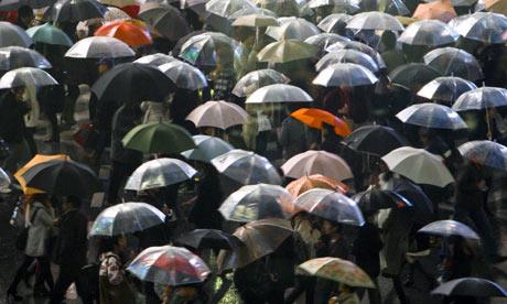 Pedestrians walk in a rain with their umbrellas