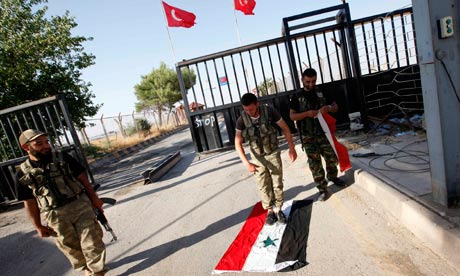 A Free Syrian Army soldier steps on a Syrian flag at the Bab Al-Salam border crossing to Turkey