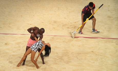 Dancers entertain the crowds as the court is raked at the beach volleyball at Horse Guards Parade