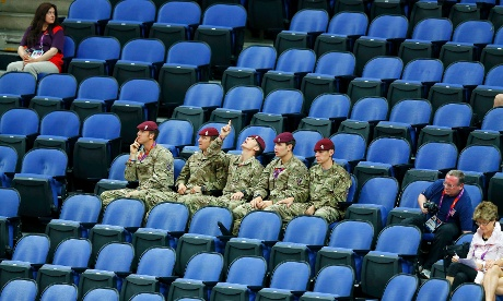 Plenty of room for these guys: soldiers sit in the empty seats held by the IOC as they watch the women's gymnastics qualification in the North Greenwich Arena this morning. Photograph: Mike Blake/ Reuters