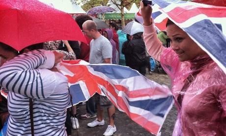 Spectators take shelter under Union Jack ponchos