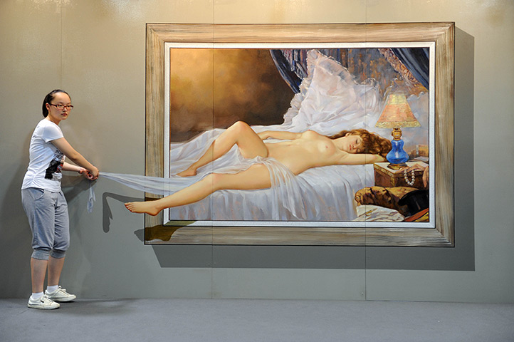 3D art China: People pose with a 2012 Magic Art Special Exhibition Of China