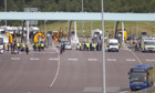 Megabus passengers are cordoned off near the M6 toll plaza after being evacuated by armed police