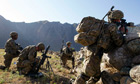 British soldiers take cover behind a stone wall in Afghanistan's Kunar province
