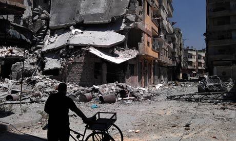 A Syrian man looks at destroyed buildings in Khaldiyeh, Homs