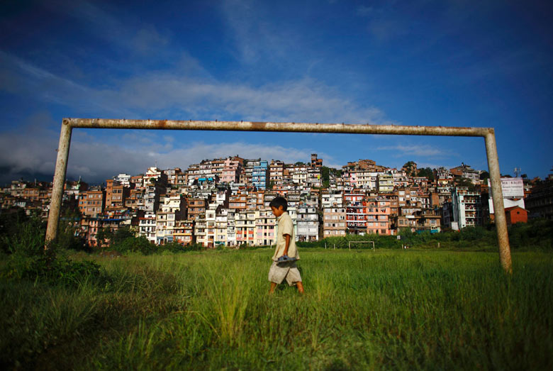 A boy walks past a football post near the ancient city of Kirtipur