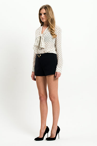All Ages: Monochrome: Model wears white blouse with black pattern and black shorts