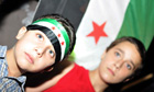 Two boys stand in front of the old Syrian flag in the northern Lebanese port city of Tripoli