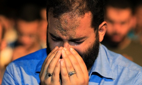 A man cries during Taraweh prayers last night during the holy month of Ramadan in Cairo's Tahrir Square.