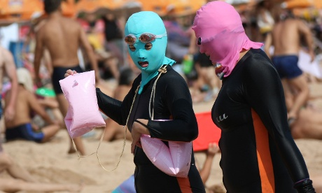 Chinese beachgoers wearing bodysuits and protective masks, dubbed 'face-kinis' by Chinese netizens, on a crowded public beach in Qingdao, north-east Shandong province. The masks were designed to protect from sunburn. but it turns out they are also quite handy at repelling insects and jellyfish.