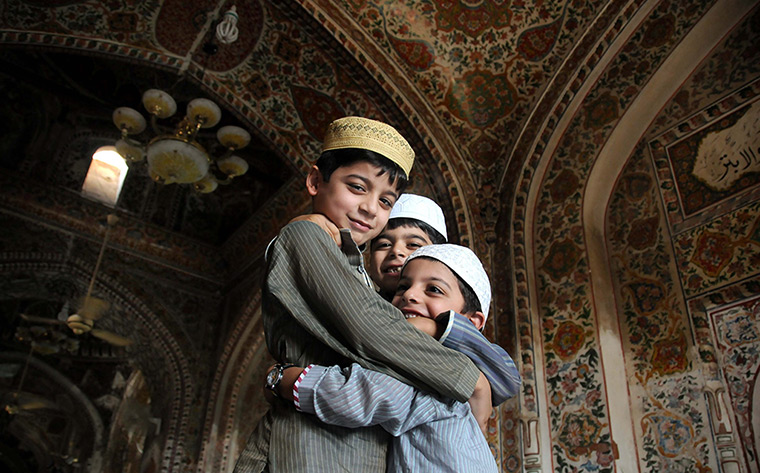Eid al-Fitr begins: Pakistani Muslim children greet each other at a mosque in Peshawar