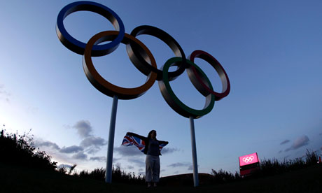 A visitor to Olympic Park poses with a set of Olympic Rings