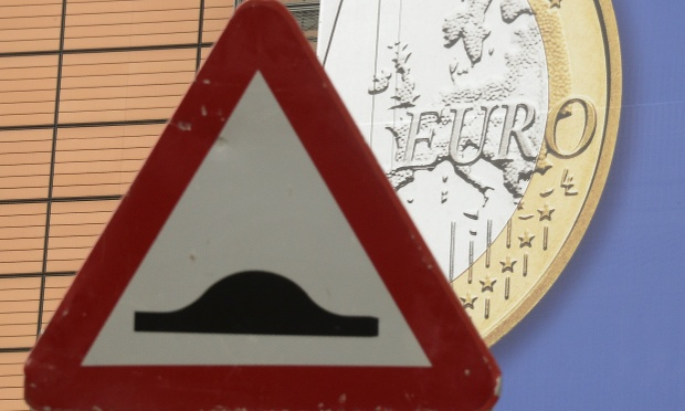 A traffic sign is seen in front of an Euro coin pattern in Brussels, capital of Belgium on Aug. 20, 2012.