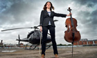 A woman stands by a helicopter with her Cello