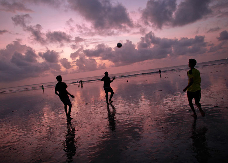 Men play football on Juhu Beach in Mumbai