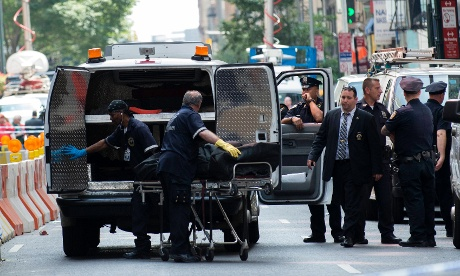 A body is moved by the New York City coroner near the site of the Empire State building where a gunman opened fire.