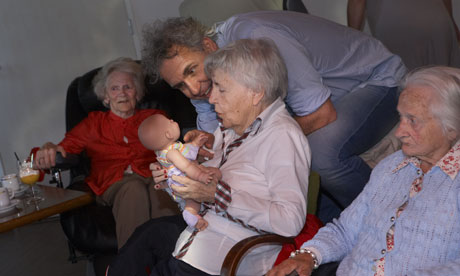 dementia village - resident plays with doll