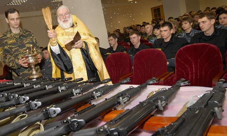 Russian orthodox priest blessing kalashnikovs