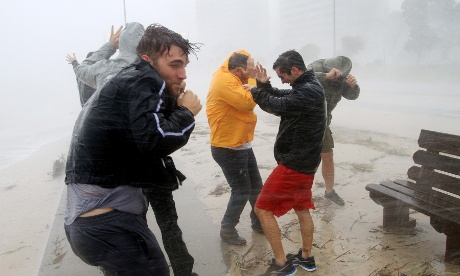 A group of friends stand against strong wind and driving rain on the beach in Gulfport as Hurricane Isaac blows.