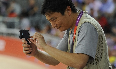 Dan Chung takes photographs using a smartphone during the track cycling events at the Velodrome. Photograph: Tom Jenkins for the Guardian
