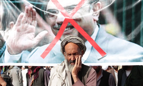 An Afghan elderly man stands in front of a poster with a cross over the portrait of Pakistan President Asif Ali Zardari, during an anti-Pakistan demonstration in Kabul, today. The Afghans were demonstrating against mortar firing from Pakistan into Afghan territories.