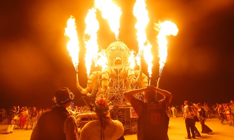 Away from the wind and rain in the east, participants watch the flames from El Pulpo Mecanico during the Burning Man 2012