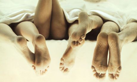 Four pairs of feet in a bed