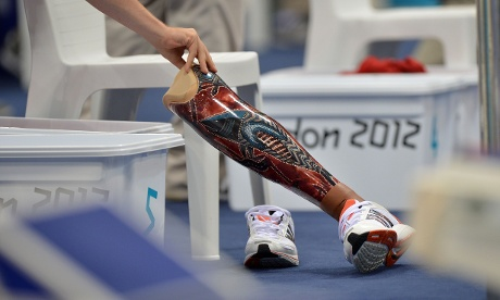 A volunteer moves a prosthetic leg belonging to Belgium's Sven Decaesstecker during the men's SM10 200m individual medely swimming heats during the London 2012 Paralympic Games at the  Aquatics Centre