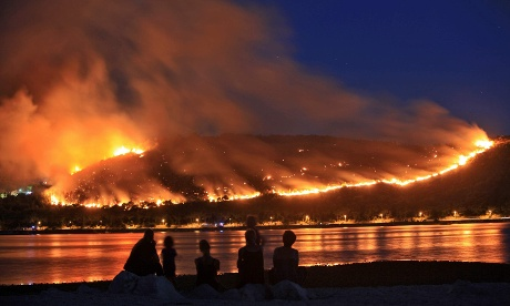 People watching the hillsides ablaze with wildfires on Adriatic coast in Croatia
