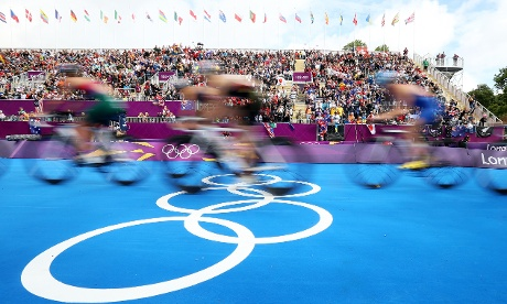 Athletes pass the crowds in the cycling leg of the Women's Triathlon
