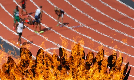 The cauldron is seen over the track after the men's 100 metre heat